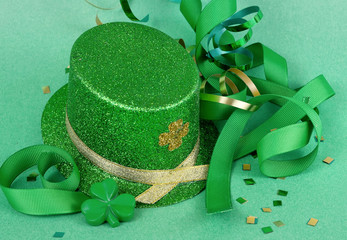 Saint Patrick's Day image of sparkly green and gold leprechaun hat with curls of green and gold ribbon on a green background with confetti scattered around.