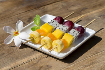 Fresh tropical fruit on skewers in white plate - healthy breakfast, weight loss concept. Thailand