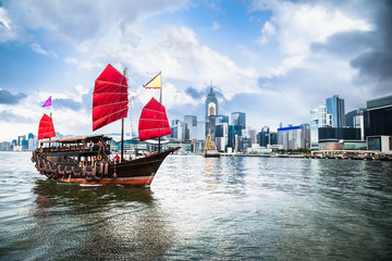 Traditional Chinese wooden sailing ship with red sails in Victoria harbor, Hong Kong.