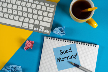 Good morning - is written on small notepad with a cup of coffee, pen, keyboard on bright workplace at office or home