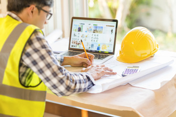 architect man working with laptop and blueprints,engineer inspection in workplace for architectural plan,sketching a construction project.