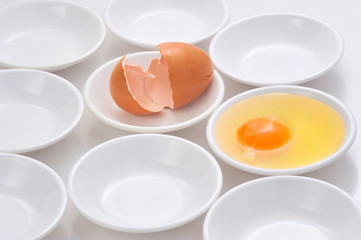 yolks in small bowls  by circle shape repetition in white background.