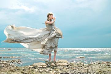 woman in a gray silk dress, fanned by the wind on the ocean