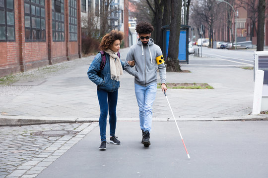 Woman Helping Blind Man While Crossing Road
