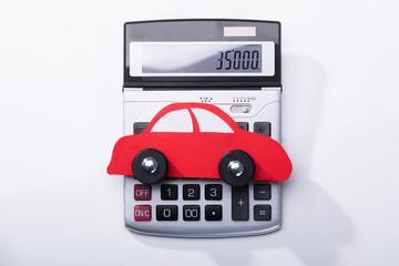 Close-up Of Red Car And Calculator