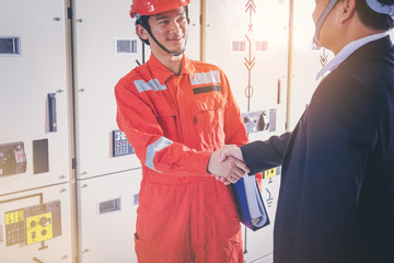 Electrical and instrument technician and businessman shake hand in front of electric system.