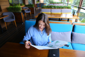Young lady resting at restaurant and reading menu with close up face  . Beautiful woman sitting on sofa in blue shirt with satisfied smile and casual make up. Concept of gladden cafe customers an