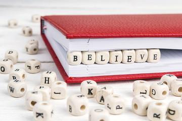Word Believe written in wooden blocks in notebook on white wooden table.