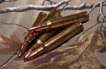 Five rifle bullets on a camouflage background