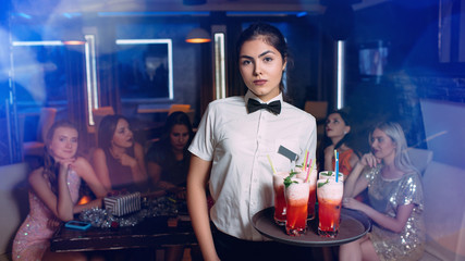 Restaurant or bar service. Young waitress catering customers with cocktail drinks. VIP service