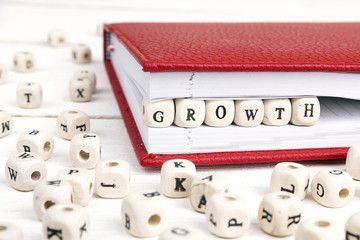 Word Growth written in wooden blocks in notebook on white wooden table.