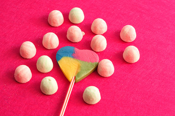 A heart shape lollipop displayed with sugary marshmallows