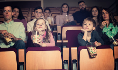 Emotional audience eating popcorn and enjoy watching movie