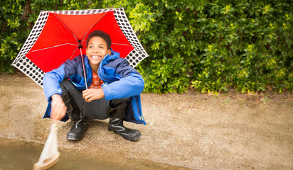 Happy African American boy with umbrella, playing with sailboat. copy space