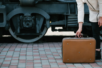 travel fashion accessories. hipster vintage retro suitcase style. transport journey destination. woman at a railway station. free space concept