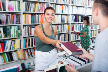 Smiling girl getting help with book choice