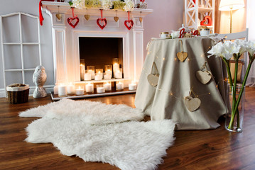 Interior for the celebration of St. Valentine's Day. A cozy and romantic atmosphere in a heart decorated room with a fireplace and candles.