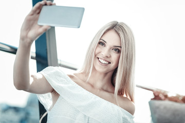 My photo. Cheerful happy nice woman looking into the smartphone camera and smiling while taking a photo of herself
