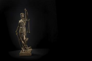 Wunderschöne römische Justitia Statue im Scheinwerferlicht vor schwarzem Hintergrund