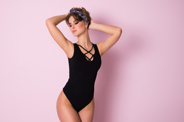 Beautiful sexy girl black bodysuit standing on a pink background.
