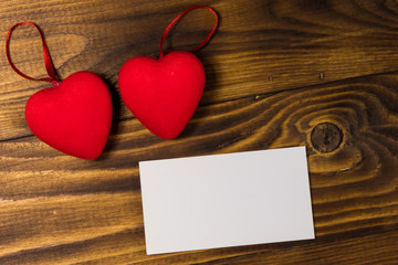 Valentine's day blank greeting card and two red hearts on wooden background