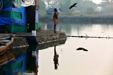 A fisherman brushes his teeth as he stands outside a temporary shelter on the bank of Periyar River, on the outskirts of Kochi
