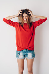 Frustrated young woman tearing at her long hair