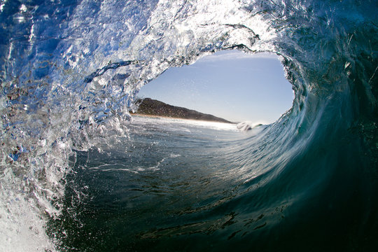 Inside view of wave breaking with tropical island view in background