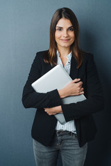 Attractive businesswoman clutching a laptop