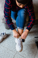 Young Woman with Dreadlocks Putting On Sneakers Shoes to Go Out