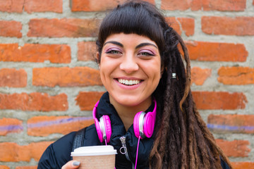 Urban Young Woman with Dreadlocks and Pink Headphones Smiling at Camera
