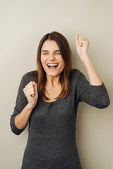 Jubilant excited young woman cheering