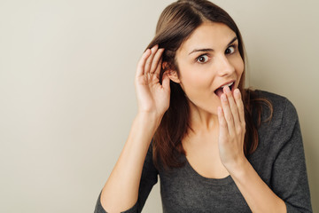 Astonished young woman listening to gossip