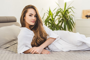 pretty young woman in bathrobe resting on bed at home