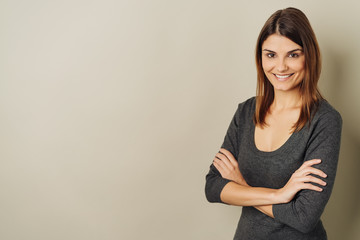 Happy vivacious young woman with folded arms
