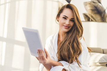 portrait of young woman in bathrobe with tablet sitting on bed at home