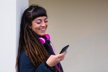 Urban Young Woman with Dreadlocks using a Mobile Phone Outdoors