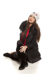 Young woman in winter clothess sitting on the floor
