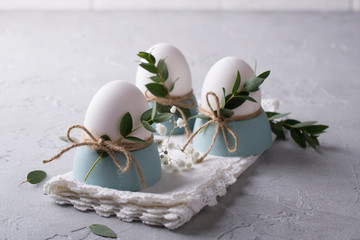 White chicken eggs with easter decor on a white napkin. Home decor trend