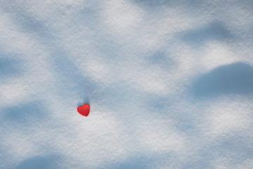Small red heart and fresh untouched snow background