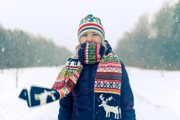 Portrait of girl in knitted hat in winter forest