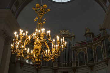 Detail of a luxury chandelier with golden decorations and hanging in a Christian cathedral. There are many lit electric candles that illuminate the church.