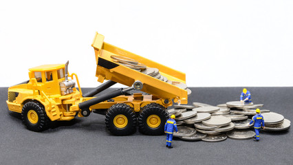 miniature technician team with a truck dumps coins money to ground