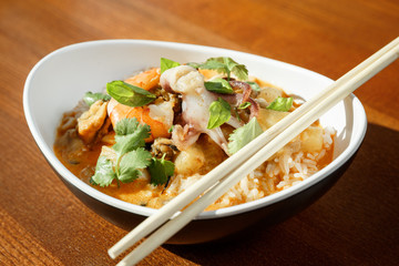 Asian riсe with seafood - shrimps and octopus -with sause in oval plate with bamboo sticks