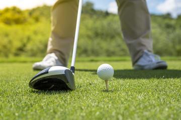 Golfer put golf ball on tee preparing shot on to golf hole