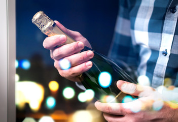 Man about to open and pop champagne bottle or sparkling wine. Festive celebration and party concept. City lights reflected in hotel or luxury home window at night.