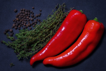 Two red chili peppers with a bunch of thyme and black pepper on a dark background.