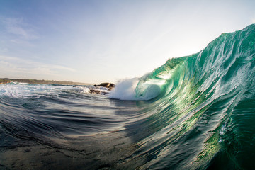 emerald green wave breaking over a shallow reef Wall mural