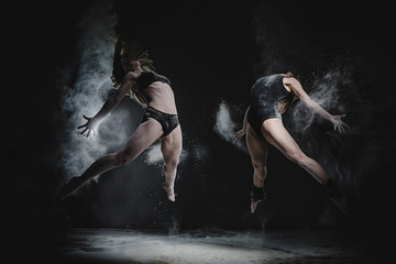 Two girls dance with flour in studio on black background, lights behind them and people helped girls