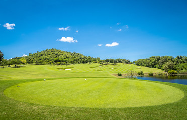Green grass and trees at golf course with blue cloud sky background